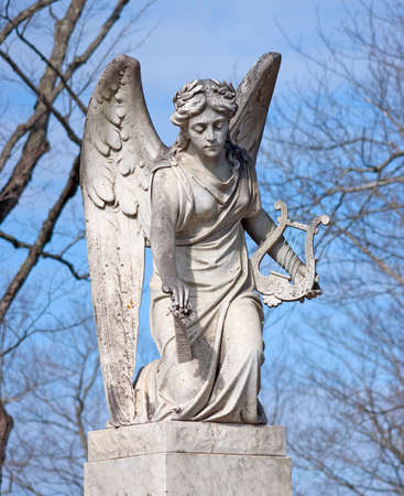 An aged statue of an angel holding a harp. photo