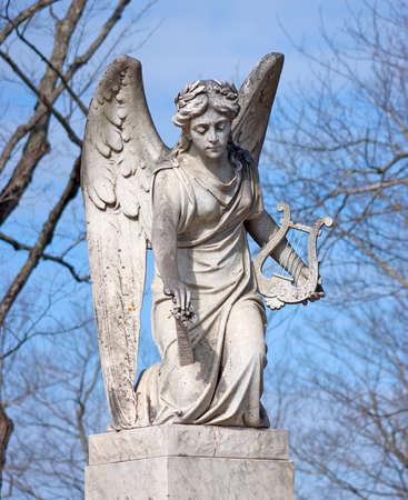Een verouderd standbeeld van een engel die een harp houdt. Stockfoto