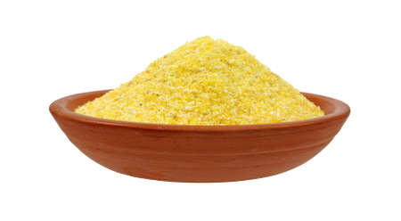 Side view of a small red clay dish filled with polenta on a white background.