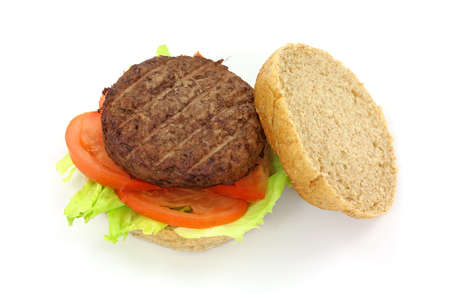 A low fat healthy hamburger on a wheat bun with cut lettuce and tomato on a white background.