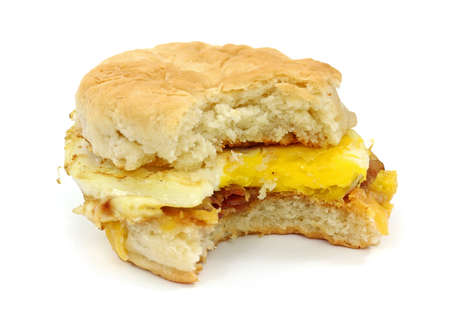 Breakfast sandwich biscuit with bacon egg and cheese that has been bitten once.  photo