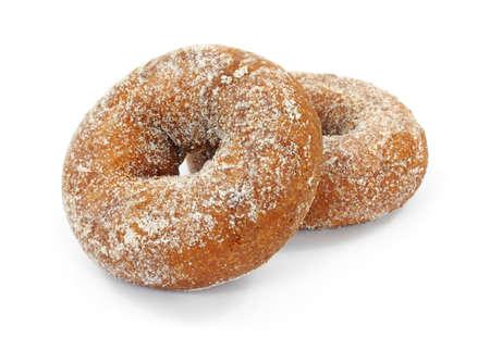 Twee cake donuts die zwaar met suiker op een witte achtergrond hebben bestrooid.