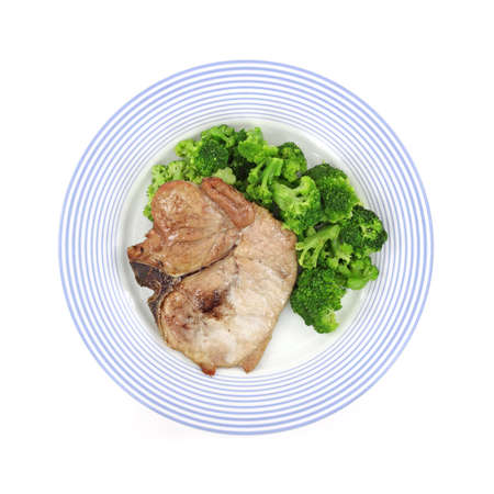 A freshly cooked pork loin chop and broccoli on a blue striped plate.
