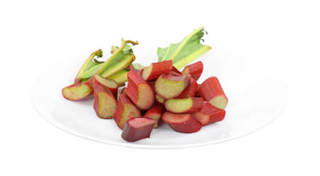 A white plate with several pieces of cut rhubarb with greens on a white background.  photo