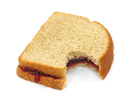 jam sandwich: A grape jelly sandwich on wheat bread that has been bitten on a white background. Stock Photo