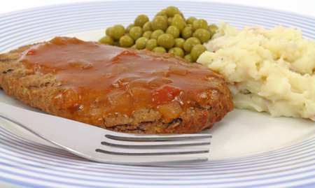 Close view of a low calorie meat loaf meal with potato and peas on a blue plate with fork. photo