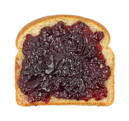 Single slice of whole wheat bread with grape jelly spread on a white background. Imagens