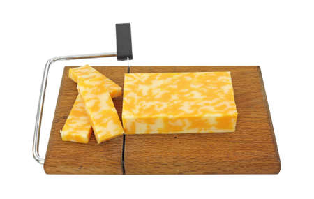 A block of Colby Jack cheese that has been sliced on a cheese cutting board.  Imagens