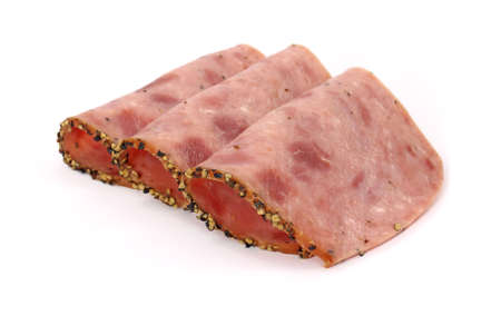 peppered: Several slices of peppered luncheon loaf deli meat folded on a white background.