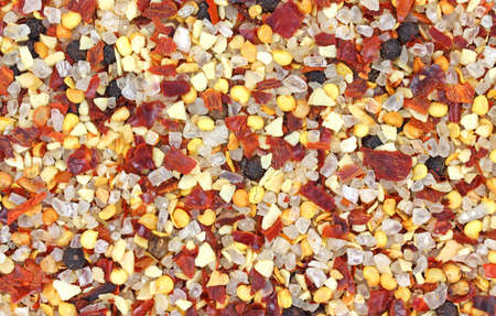 A very close view of coarsely ground red pepper, salt and whole black pepper seasoning.