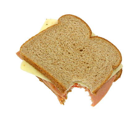 A bitten wheat bread sandwich with pickle and pimento and pepper jack cheese on a white background. photo