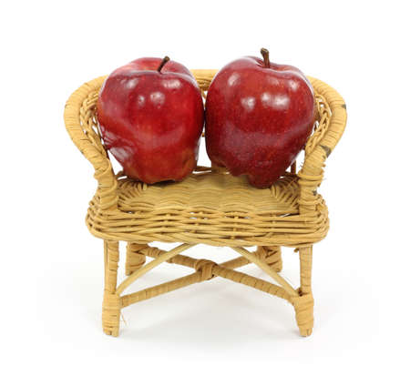 round chairs: Two red apples in a toy wicker loveseat on a white background. Stock Photo