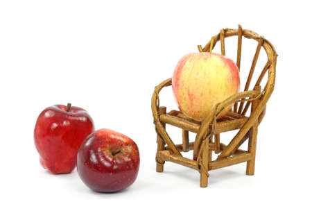 A gala apple in a toy chair at an angle with two red delicious apples in front. photo