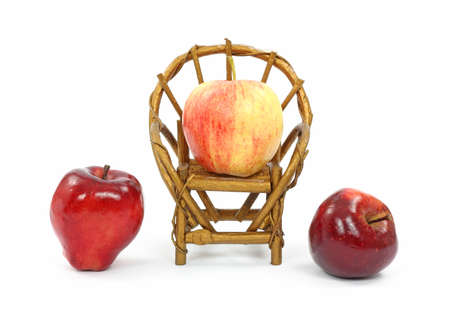 round chairs: A gala apple in a toy chair with two red delicious apples on either side. Stock Photo