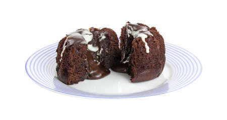 A small individual sized lava cake that has been cut in half to show the filling on a blue striped plate.  Standard-Bild