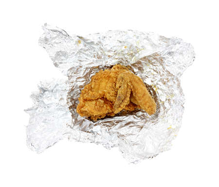 A single piece of leftover fried chicken on a large piece of aluminum foil.