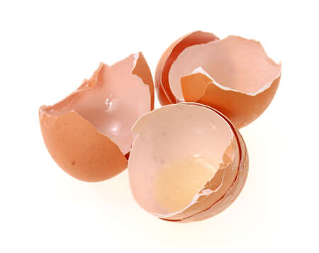 Three brown egg shells that have been cracked opened and used on a white background.