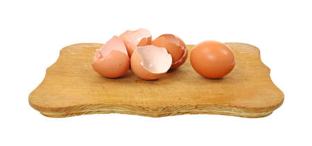 Several broken and empty brown egg shells with a single whole egg on a wood cutting board.
