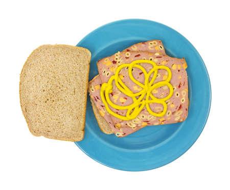Een macaroni en kaas boterhamworst sandwich op tarwe brood met mosterd in een blauwe schotel op een witte achtergrond.