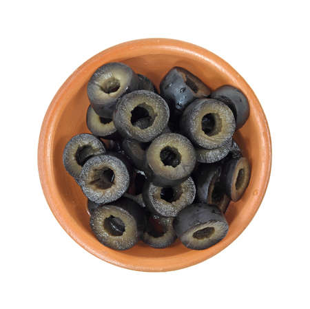 A small bowl filled with sliced black olives on a white background. 스톡 콘텐츠