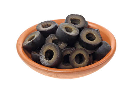 Sliced black olives filling a small clay bowl on a white background. Imagens