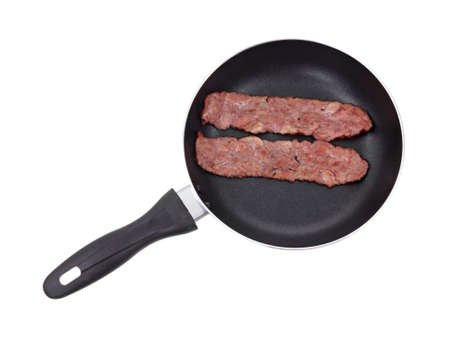 turkey bacon: A black skillet with two slices of turkey bacon cooking on a white background. Stock Photo