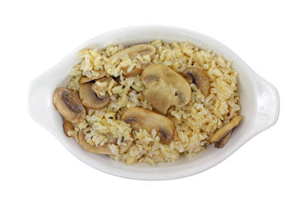 white backing: A large serving of sauteed mushrooms and cooked brown rice in a white backing dish.