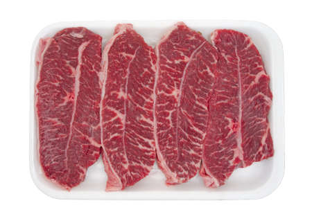 Four small boneless top blade steaks on a white foam butchers tray against a white background. 版權商用圖片