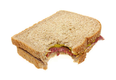 A corned beef sandwich that has been bitten on a white background.  photo