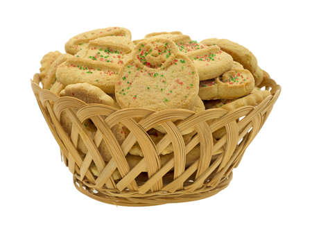 Side view of an old wicker basket filled with Christmas butter cookies.  photo