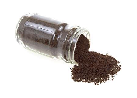 freeze dried: Vista lateral de un frasco de vidrio de caf� instant�neo con algunos de los gr�nulos de derramar en un fondo blanco. Foto de archivo
