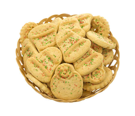 An old wicker basket with butter Christmas cookies on a white background.  photo