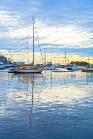 Early morning view of a harbor with boats, wispy clouds, yellow sky and reflective water.