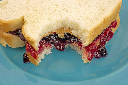 A close view of a peanut butter and jelly sandwich on a blue plate that has been bitten. Stock Photo
