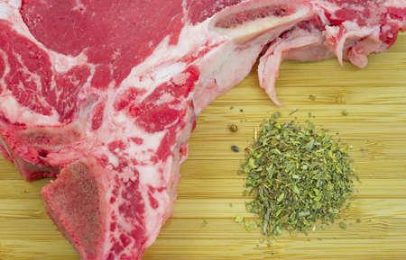 Een zeer dichte mening van een deel van een t-bone steak met kruiden op een houten snijplank. Stockfoto - 11600754