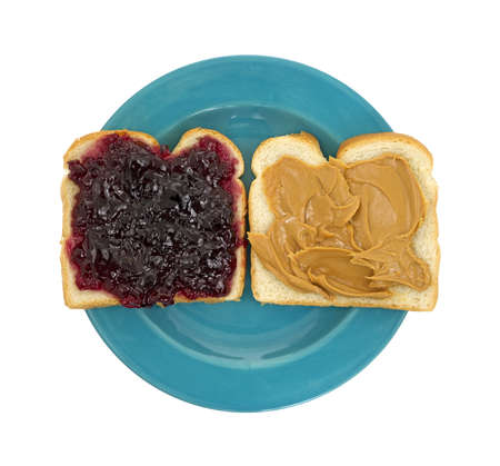 A peanut butter and jelly sandwich open faced on a blue plate.