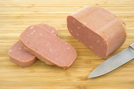 luncheon: Close view of canned luncheon meat with blade of knife on a wood cutting board.  Stock Photo