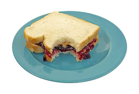jelly sandwich: A peanut butter and jelly sandwich that has had one bite on a blue plate against a white background.