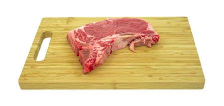 Side view of a t-bone steak on a wood cutting board.