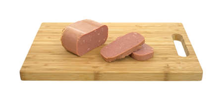 luncheon: Side view of a wood cutting board with a chunk of canned meat and two slices on a white background.