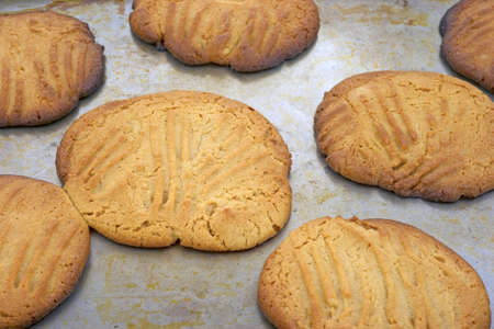 overly: Close view of several overly baked peanut butter cookies on a baking pan.