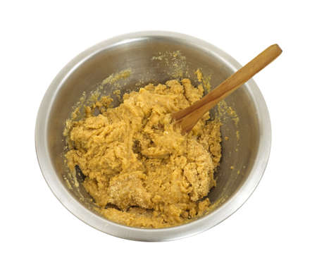 Een roestvrijstalen kom met gemengde up koekjesdeeg en roeren lepel op een witte achtergrond. Stockfoto