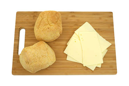 Top view of sharp cheddar cheese slices with two small French rolls on a wood cutting board. Stok Fotoğraf