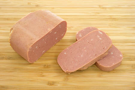 luncheon: Close view of canned meat with two slices on a wood cutting board.