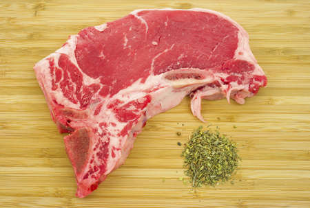 A fresh t-bone steak on a wood cutting board with seasoning.