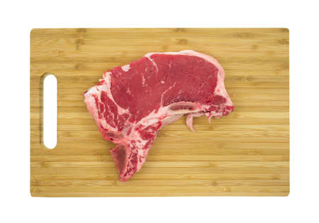 Top view of a fresh t-bone steak on a wood cutting board. photo