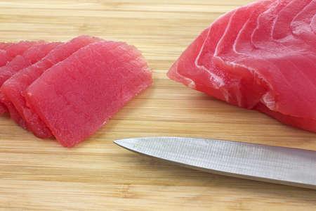 atun: Cerrar la vista de varias piezas de atún aleta amarilla en rodajas sobre madera tabla para cortar con cuchillo.