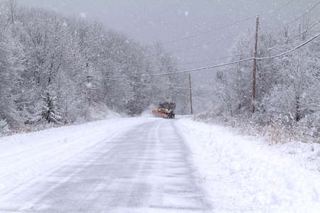 wintery day: A snowy wintery day with road and snowplow in the distance.