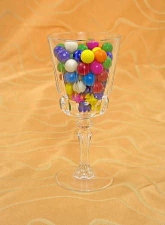 A wine glass filled with bubble gum on a gold cloth background.  photo