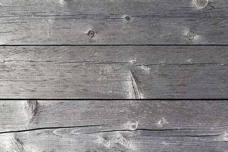 weathered: Close view of three grayed and weathered boards.